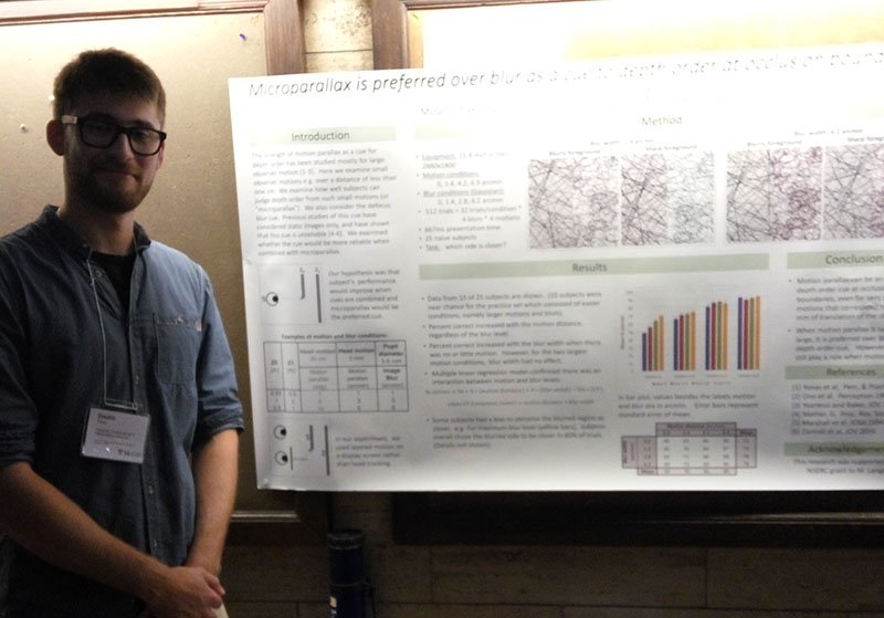 Dmitrii Tiron standing in front of the poster he created detailing his research